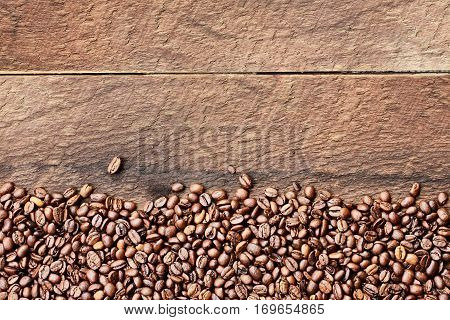 Overhead shot looking down on a flatlay image of coffee beans over a rustic wood table top background with copy space.