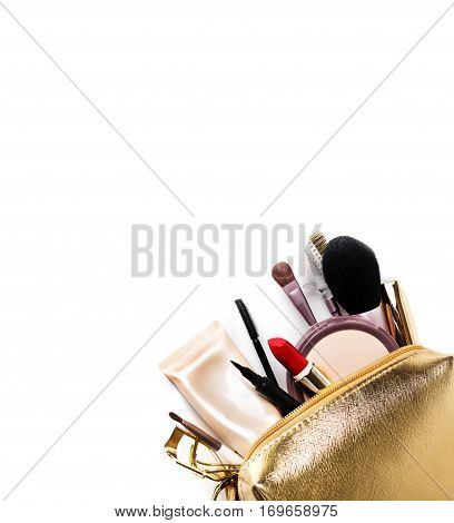 Women's cosmetics. Gold cosmetic bag with a set of cosmetics to create a make-up on a white background. Copy space.