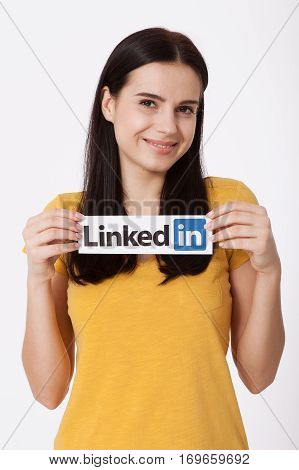 KIEV, UKRAINE - August 22, 2016: Woman hands holding Linkedin logo sign printed on paper on white background. Linkedin is a business social networking service.
