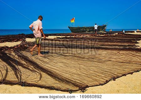 Goa, India - November 17, 2012: Unidentified fishermen dried his old fisher's net. Beaches in Goa are state-owned so the hotels do not have the right to prohibit boats and nets drying on the beaches