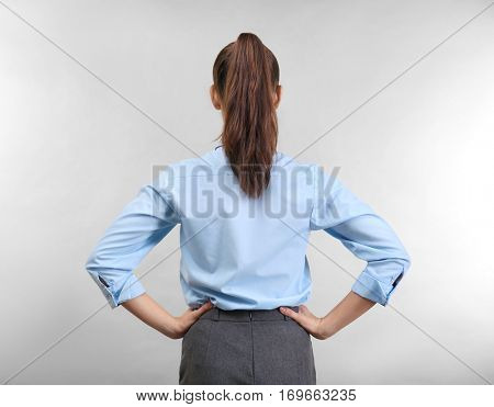 Confident young woman on light background