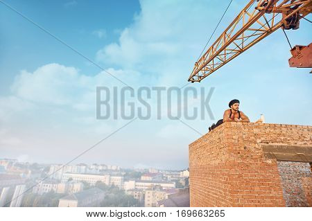 Tired and handsome builder in hat lying on brick wall on high and resting. Looking away. Blue sky with clouds at summer season on background. Milk and bread near.