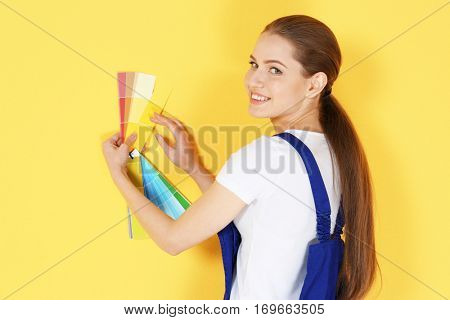 Beautiful young decorator selecting color of wall, on yellow background
