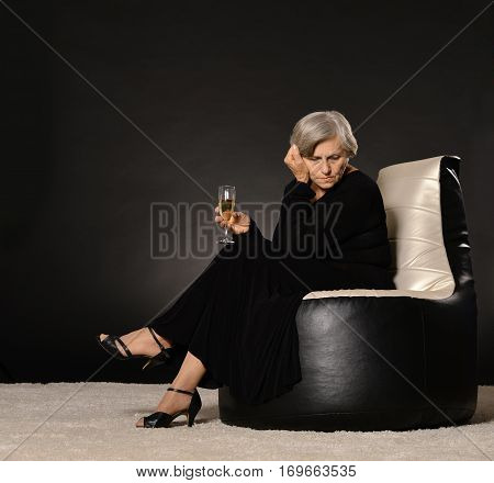 Sad Elegant woman drinking champagne on dark background