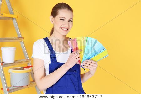 Beautiful young decorator with color samples on yellow background