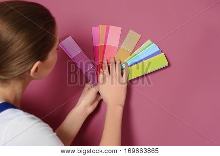 Beautiful young decorator selecting color of wall
