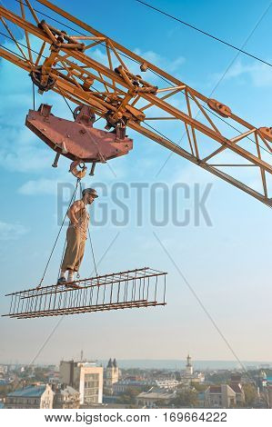 View from distance of athletic builder in work wear standing on construction on high. Building crane holding construction with man over city. Extreme building of house in big city. Man looking down.