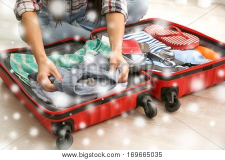Winter vacation concept. Snowy effect on background. Woman packing stuff into suitcase at home