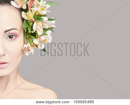 Beautiful Nude attractive brunette with flowers on his head. Fashion beautiful makeup clean skin facial care. Portrait of young beautiful woman with perfect skin