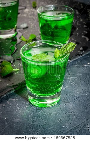 Sweet refreshing mint liqueur with ice and mint leaves on the slate tray to feed on gray concrete stone table close view