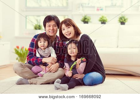 Young Happy Family With Pretty Daughters Playing And Having Fun At Home