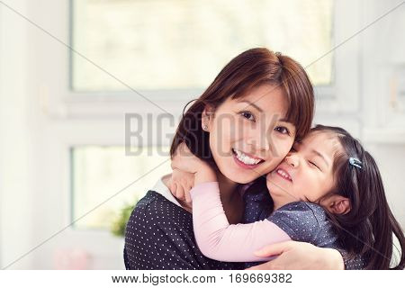 Portrait Of Happy Mother Hugging With Her Cute Little Daughter At Home