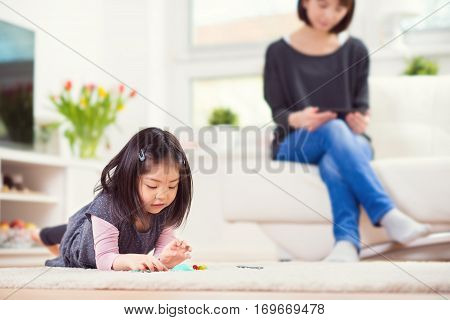 Cute Little Girl Playing On Carpet And Mother Sitting With Tablet In Background