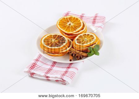 plate of dried oranges slices with cinnamon and anise on checkered dishtowel