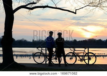 Silhouettes of couple watching sunset at Jefferson memorial - Washington DC USA