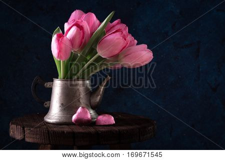 Fresh Pink Tulip Flowers Bouquet In Old Teapot With Chocolate Heart.