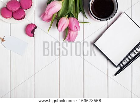 Pink Tulips, Macarons, Empty Notepad And Coffee On White Wooden Table.
