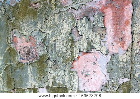Tatter of a multi-colored old paint on a surface of a stone wall