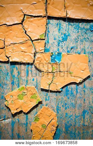 Large fragments of old peeling paint color ocher, on an old wooden weathered surface.