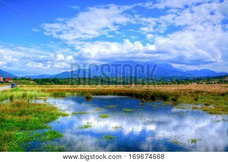 Beautiful spring landscape with clouds and mountain reflected in a lake in Bran area, Romania