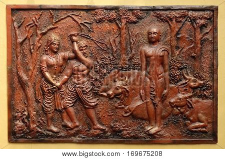 KOLKATA, INDIA - FEBRUARY 09, 2016: Indra prevents an ignorant cowherd from assaulting Bhagavan Mahavira, Street bas relief on the wall of Jain Temple (also called Parshwanath Temple) in Kolkata