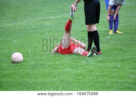 Referee provides assistance injured player at the football match