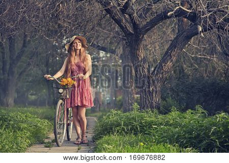 photo with artistic effect. vintage toning. film retro style. young woman in a hat with a bike in the park . Active people. Outdoors