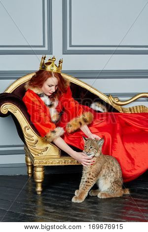 Red-haired woman in red dress, cloak and with crown on head lies on couch and lynx cub sits near on floor.