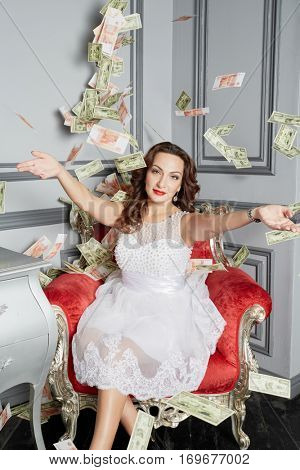 Woman in white dress sits in armchair at room under money banknotes shower.