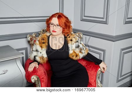 Red-haired woman in black dress anf fur mantle sits in red armchair in room.