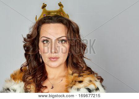 Portrait of woman in fur cloak and queen crown.