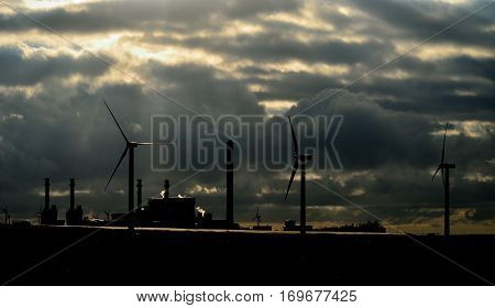 Power plant and wind turbines with clouds background at dawn