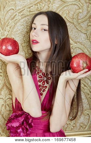 Portrait of young girl with two pomegranites in hands.