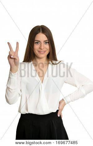 Beautiful woman in white blouse gesturing winner sign on white background