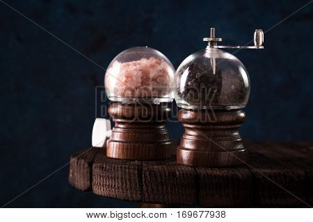 Salt and pepper mills on wooden background