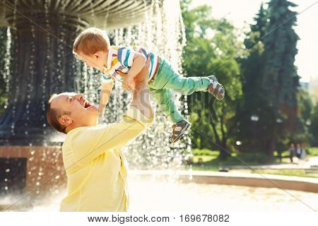 outdoor portrait of father and son. child and dad walk in the summer park