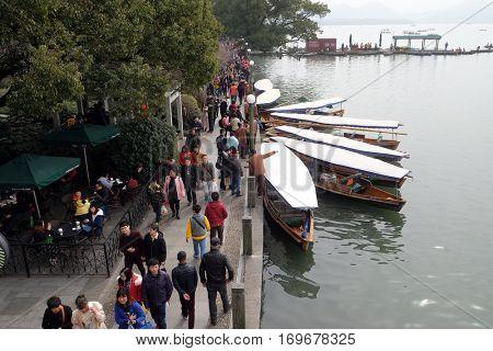HANGZHOU - FEBRUARY 21: Crowd of tourists and boatmen on West Lake coast, famous park in Hangzhou city, China, February 21, 2016.