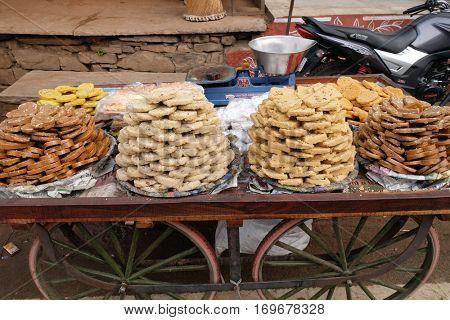 PUSHKAR, INDIA - FEBRUARY 18: A street vendor selling sweets outside the Jagatpita Brahma Mandir Rama temple in Pushkar, India on February 18, 2016.