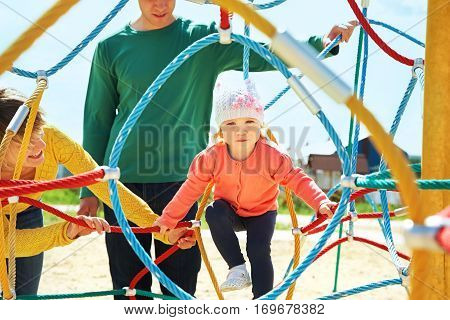 outdoor portrait of a child with parents at the playground. Mom, dad and child
