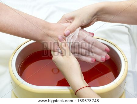 Process paraffin treatment of female hands in beauty salon