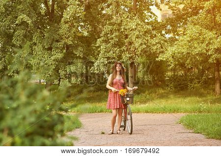 young woman in a dress and hat with a bike in a summer park. Active people. Outdoors