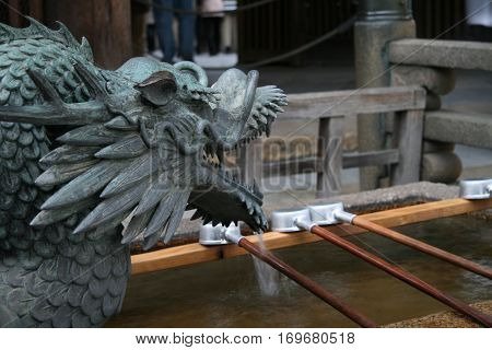 Dragon fountain of Japanese Tsukubai at an old temple - provided at the entrance to holy places for visitors to purify themselves by the ritual washing of hands and rinsing of the mouth
