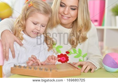 mother with little daughter playing on instrumen