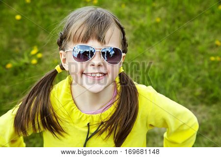 cheerful girl in sunglasses in the park. children outdoors. vacation in the summer park