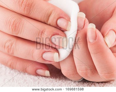 Woman using cotton pads to remove nail polish