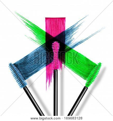 Strokes of colored mascara with brushes close-up on white background