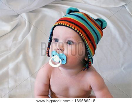 Baby boy in bright hat with pacifier