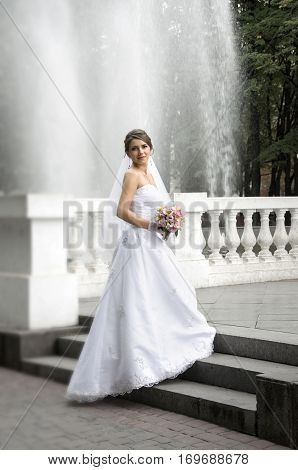 Beautiful bride in white dress with wedding bouquet against the fountain