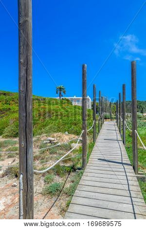 Wooden path to Playa de Son Bou Beach on sunny summer day at Menorca island, Spain. Travel background.