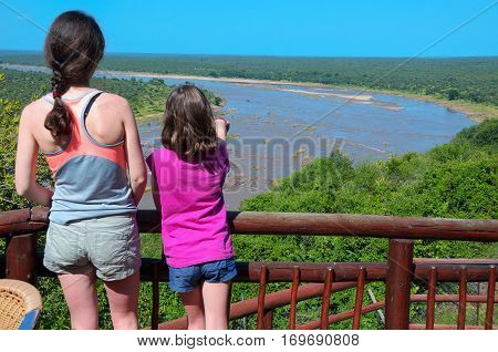 Family safari vacation in South Africa, mother and daughter looking at beautiful river view, tourists travel Kruger national park